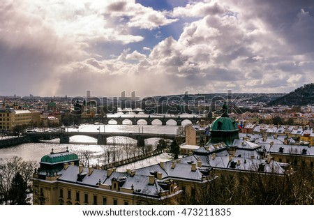 Amazing towers of Charles bridge and old town district with several bridges at Vltava river during winter day. Heavy snow storm and sun rays peeping through clouds, Prague, Czech republic #473211835