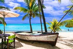 amazing tropical holidays. Beach seaside restaurant with old boat. Mauritius island
