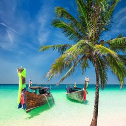 Amazing tropical landscape with Thai traditional wooden boats and palm tree at ocean beach under blue sky. Thailand travel