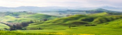 Amazing Tuscany panoramic landscape with green rolling hills in spring sunny morning