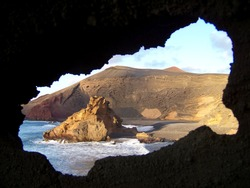 Amazing view at the black beach and the rock in the ocean from the hole with blurry edge in the mountain in Lanzarote, Canary islands. The outline of the hole reminds the shape of the island