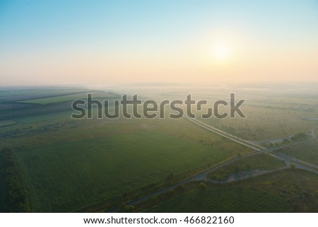 Amazing view from the height of the balloon. Summer beautiful fields landscape from the bird's eye, sunrise. Ballooning.