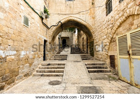 Amazing view of a small alley surrounded by the walls of the Old city of Jerusalem, Israel. The Old City is a 0.9 square kilometres walled area within the modern city of Jerusalem.
