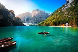 amazing view of braies lake with wooden boats on the water, surrounded by dolomites mountains. Trentino alto adige, Italy
