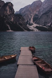Amazing view of Lago di Braies (Braies lake, Pragser wildsee). Trentino Alto Adidge, Dolomites mountains, South Tyrol, Italy, Europe. Boats at the lake. Fanes-Sennes-Braies national park. brown boats