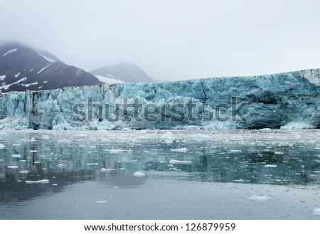 Amazing view of melting blue glacier, calm water and black mountain covered with snow against the background cloudy grey sky with heavy fog in Spitsbergen (Svalbard island), Greenland Sea, Norway