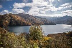 Amazing view of the Goy-Gol (Blue Lake) Lake among colorful fall forest at Ganja, Azerbaijan. A calm evening landscape with lake and mountains