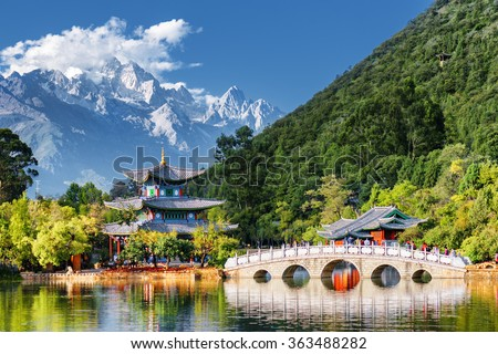 Amazing view of the Jade Dragon Snow Mountain and the Black Dragon Pool, Lijiang, Yunnan province, China. The Suocui Bridge over pond and the Moon Embracing Pavilion in the Jade Spring Park. #363488282