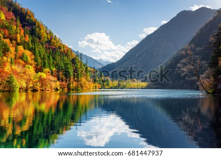 Amazing view of the Panda Lake among colorful fall forest at the Rize Valley in Jiuzhaigou nature reserve (Jiuzhai Valley National Park), China. Scenic wooded mountains and blue sky reflected in water - Shutterstock ID 681447937
