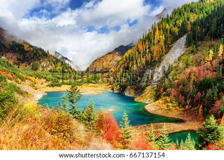 Stock Photo Amazing view of the Upper Seasonal Lake with azure water among colorful fall woods and mountains in fog, Jiuzhaigou nature reserve (Jiuzhai Valley National Park), China. Scenic sunny autumn landscape.