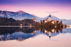 Amazing View On Bled Lake on Sunset. Autumn in Slovenia, Europe. View on Island with Catholic Church in Bled Lake with Castle and Mountains in Background.