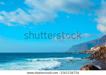 Amazing view on ocean waves on the coast of the island at summer sunset. Seaside resort.