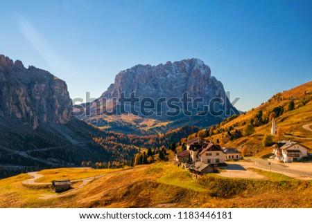 Amazing view on Sassolungo - Langkofel - mountain and Gardena Pass ander autumn sun. Dolomite Alps, South Tyrol, Italy.