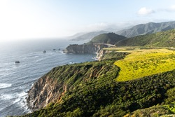 Amazing view on the green hills, waving ocean and Bixby Creek Bridge in the spring with a clear blue sky. California, USA
