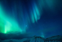Amazing view on the Northen light over high mountains covering with snow, forces of nature, Aurora Borealis, Iceland