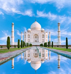 Amazing view on the Taj Mahal in sun light with reflection in water. The Taj Mahal is an ivory-white marble mausoleum on the south bank of the Yamuna river. Agra, Uttar Pradesh, India.