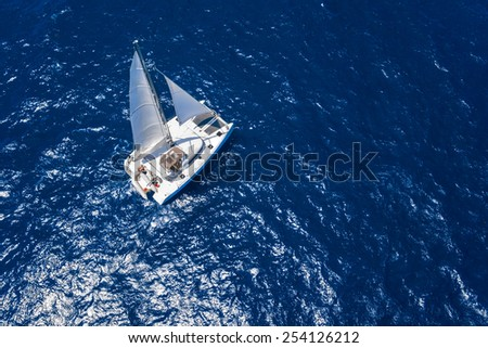 Amazing view to Catamaran cruising in open sea at windy day. Drone view - birds eye angle #254126212