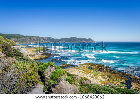 Amazing view to stunning rocky sandy beach deep blue water of southern ocean antarctica on warm sunny day with blue sky after hiking on to South Cape Bay, South-West National Park, Tasmania, Australia #1068420062