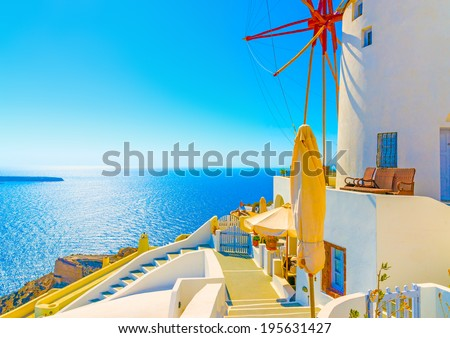 Amazing view to the sea including a pictorial old traditional windmill in Oia the most beautiful village of Santorini island in Greece #195631427