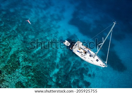 amazing view to yacht, swimming woman and clear water caribbean paradise