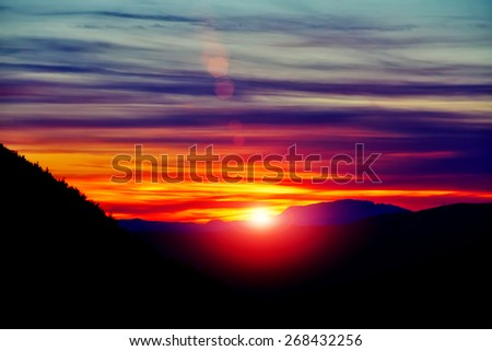 Amazing view with colorful sunset and sun rays over mountain landscape