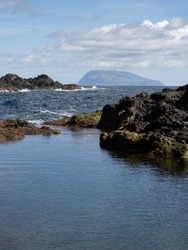 Amazing view with the contrast between rough and calm waters in the natural pools of Santa Cruz das Flores, of volcanic origin. In the background the remote island of Corvo. Flores Island.