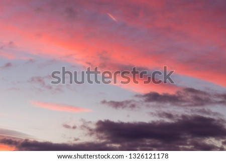 Amazing vivid colors of a sunlit, contrasty clouds on a sunset sky #1326121178