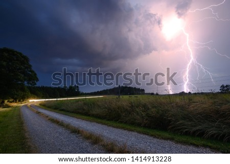 Amazing Weather Storm Photo with Big Bright Pink Lightning Bolt Strike Coming from Dark Moody Sky with Gray Clouds and Car Driving in Driveway Beside Green Field in Summer #1414913228