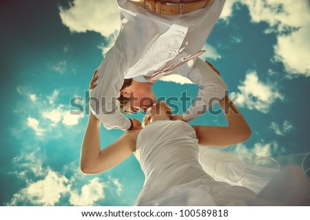 Amazing wedding couple kissing against the backdrop of the beautiful sky.