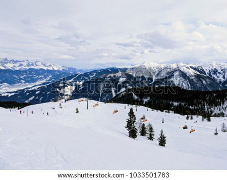 Amazing winter landscape with snow covered mountain peaks in the austrian alps. Austrian sky resort with long ski slopes. Skiers on the slope and on the chair lift traveling to the top. Winter sports #1033501783