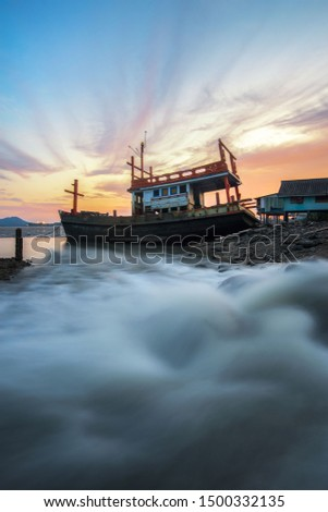 Amazing wooden boat on the sea and beautiful sunset ,motion blur on foreground or wave due to slow shutter speed shot. Composition of nature. Seascape water rushing around, phuket Thailand.