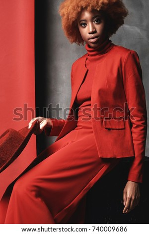 Amazing young black serious model female with red hair wearing red wide pants, jacket, sweater and shoes sitting in studio with grey and red background and holding red hat #740009686
