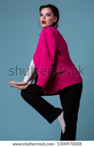 Amazing young brunett woman in trendy pink jacket standing on one leg, looking at the camera posing in the studio on blue background #1300970008