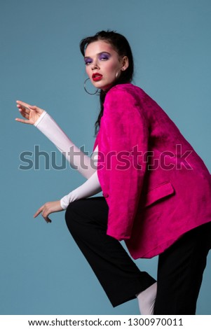 Amazing young brunett woman in trendy pink jacket standing on one leg, looking at the camera posing in the studio on blue background #1300970011