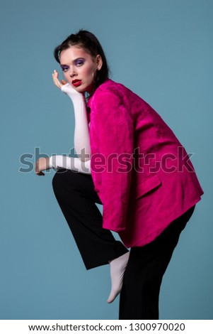 Amazing young brunett woman in trendy pink jacket standing on one leg, looking at the camera posing in the studio on blue background #1300970020