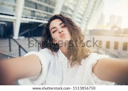 Amazing young woman stand alone outside and hold camera with both hands. Stand alone outside. White buildings behind. Sunsetin the corner of picture #1513856750