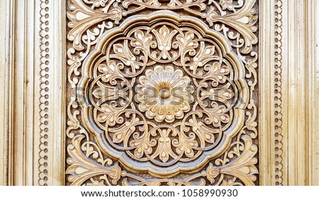amazingly beautiful traditional Uzbek floral ornament carved on the wooden door of the mosque #1058990930