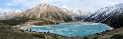 Amazingly blue Big Almaty lake covered with ice