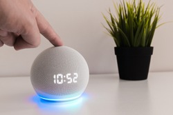 Amazon echo dot 4, voice controlled speaker with activated voice recognition, on light background and finger