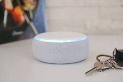 Amazon echo dot,  Voice controlled speaker with activated voice recognition with key and book white and brick background.