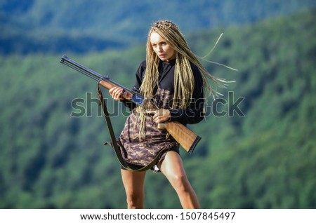 Amazon legendary race of female warriors. Hunting season. Woman attractive long hair pretty face hold rifle for hunting. Sexy warrior. She is warrior. Warrior mountains landscape background.