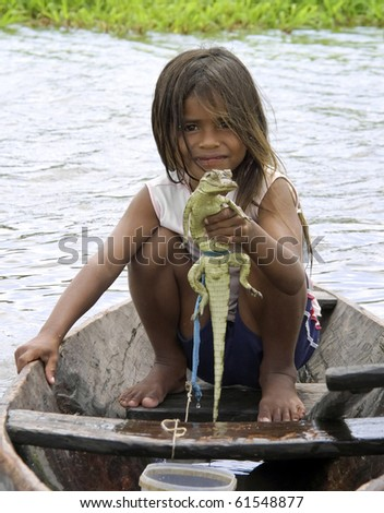 AMAZON RIVER - CIRCA SEPTEMBER 2010. Unidentified young girl holds a baby caiman at the Amazon River, Brazil, CIRCA September 2010.