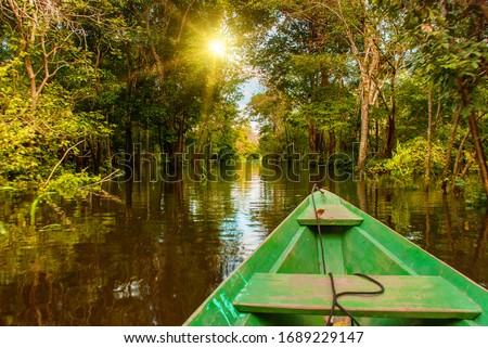 Amazon river, Manaus, Amazonas, Brazil, South America: Wooden boat floating on the Amazon river in the backwaters of the Amazon jungle.