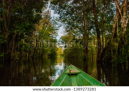 Amazon river, Manaus, Amazonas, Brazil: Wooden boat floating on the Amazon river in the backwaters of the Amazon jungle.