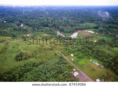 Amazonian rainforest in Ecuador, road foreground bringing colonists who have cut down the forest, but with primary forest beyond the river in the background