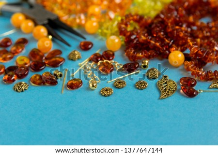 Amber beads with tools and accessories on a blue background with space for text.