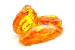 Amber. Bright yellow stone of resin on a white background. Sunstone amber texture. Mineral for jewelry. Vintage ancient resin. Baltic amber. Colored bright pieces of  resin. Amber stone texture