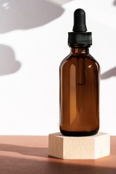 Amber cosmetic bottle on wooden geometric pedestal podium, product packaging with natural shadows from plants, anti aging serum with peptides, cosmetics mockup, biophilic concept. Front view, vertical