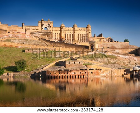 Amber Fort illuminated by warm light of the rising sun and reflected in the lake. Famous Rajasthan landmark located nearby Jaipur city in north-western India.