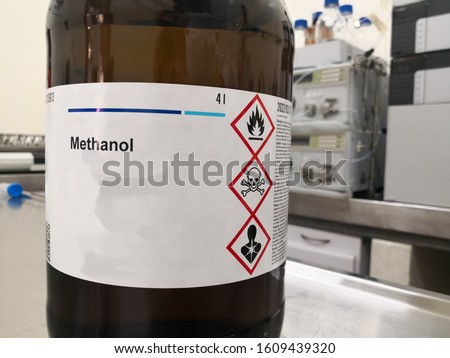 Amber glass bottle for lightning protection containing methanol, an alcohol, and a label with warnings about toxicity, flammability and death. Chemical reagent in a laboratory.
